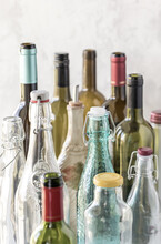 A Close Up Of Several Different Types And Sizes Of Bottles Against A Bright Background.