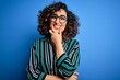 Leinwandbild Motiv Young beautiful curly arab woman wearing striped shirt and glasses over blue background looking confident at the camera smiling with crossed arms and hand raised on chin. Thinking positive.