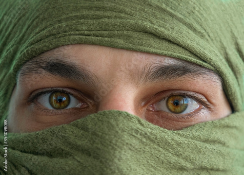 Photo close up of the green eyes of a man whose face is covered with a blue bandage