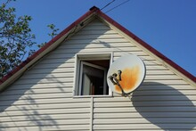 White Plastic Attic Of A Private House With One Window And A Satellite Dish Against A Blue Sky
