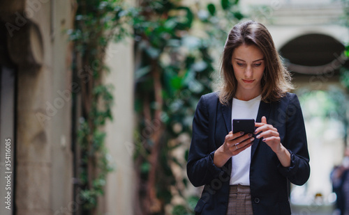 Fototapeta  hipster girl reading text business message from her managers connected to public internet outdoors, beautiful professional woman chatting on cell smartphone while relaxing outdoors obraz