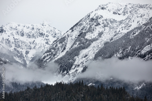 Mountain landscape of snow covered peaks and low valley clouds