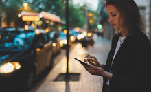 Woman Stands By Busy Road Of Evening City And Calls Smartphone Of Internet Technologies, Elegant Girl Waiting For Taxi Booking Hotel On Background Of Passing Lights Of Transport Headlights On Road