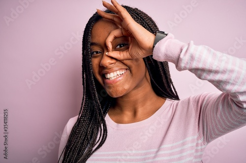Fototapeta Close up of young african american woman wearing pink sweater over isolated background doing ok gesture with hand smiling, eye looking through fingers with happy face. obraz