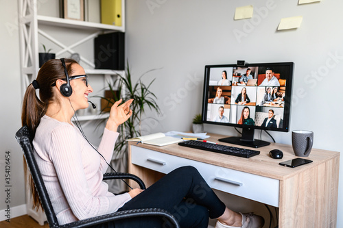 Obraz Young successful employee is have a meeting with her team using a headset, she is sitting relaxed and smiling, a middle side shot. - fototapety do salonu