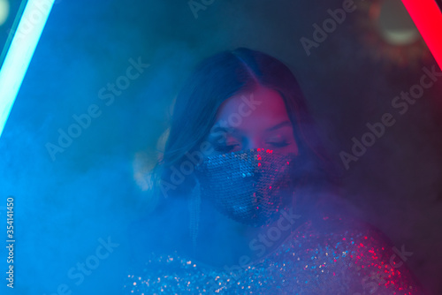 Woman wearing stylish sequin face mask posing, dancing in colorful bright neon uv blue and red lights Tableau sur Toile
