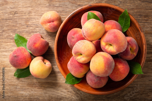 Obraz fresh ripe peaches with leaves in a bowl, top view - fototapety do salonu
