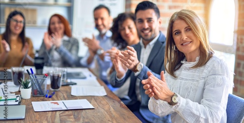 Obraz Group of business workers smiling happy and confident. Working together with smile on face looking at the camera applauding at the office - fototapety do salonu
