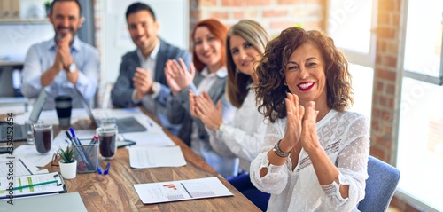 Fototapeta Group of business workers smiling happy and confident. Working together with smile on face looking at the camera applauding at the office obraz
