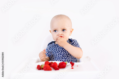 Infant girl sitting in high child's chair eating fruits on a white background Poster Mural XXL