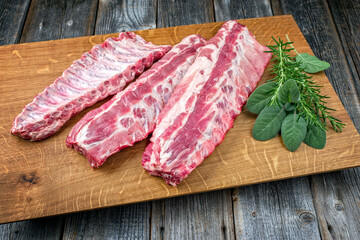 Raw pork spare loin ribs St Louis cut offered with herbs as closeup on a wooden board
