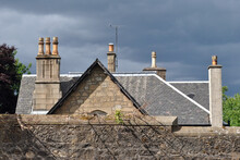 Wall Roof & Chimneys On Old Stone House Against Grey Stormy Sky
