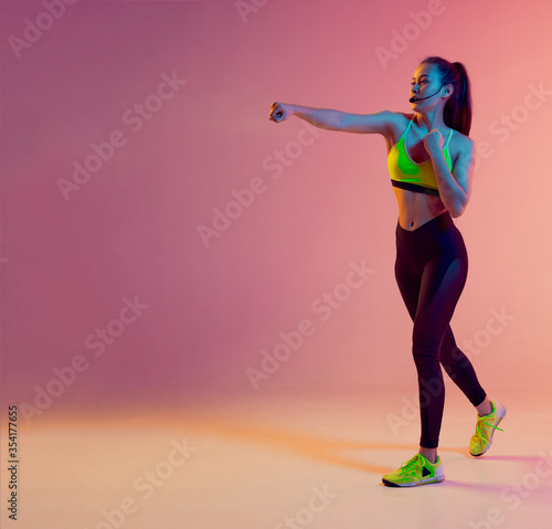 Carta da parati Cute girl fitness instructor teaches Boxing or body combat online training remotely on a bright neon background