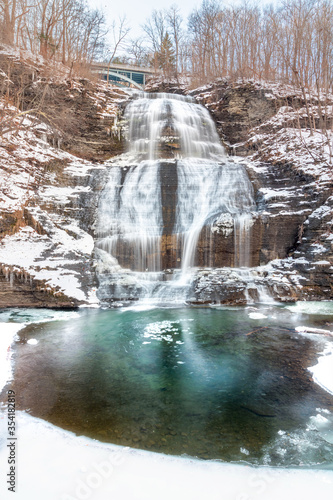 Multi tiered waterfall cascading down rocks in a snowy winter wonderland scene. She-Qua-Ga Falls - Montour Falls New York.