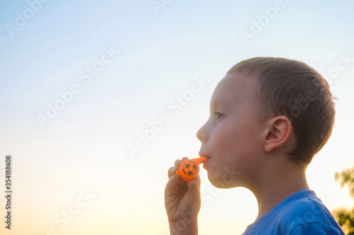 Photo Little boy diligently blowing in orange color whistle on a background of evening