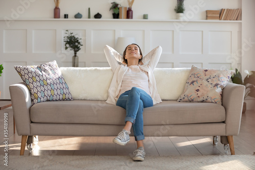 Cuadros en Lienzo Happy calm young Caucasian woman relax on comfortable modern sofa in living room