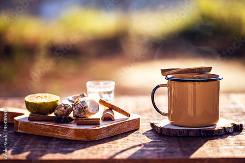 Leinwand Poster hot drink with steam, Brazilian tea called in Portuguese quentão, made with ginger, lemon, cloves, distilled alcohol, cinnamon sticks or anise