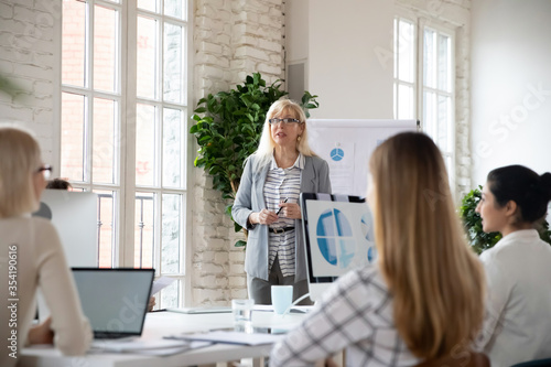 Focus on middle aged skilled female team leader presenting company growth strategy to young diverse employees Wallpaper Mural