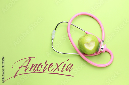 Vászonkép Stethoscope, apple and word ANOREXIA on color background