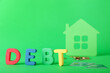 Leinwandbild Motiv Figure of house, coins and word DEBT on color background