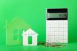 Leinwandbild Motiv Calculator, figures of house and coins on color background. Concept of debt