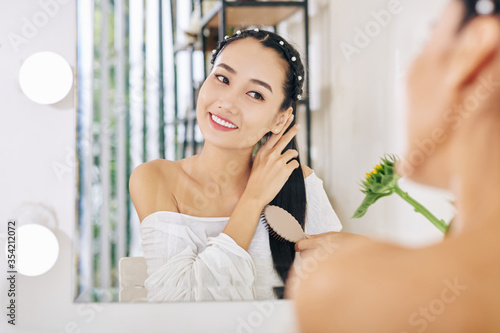 Fotografia Smiling charming young Vietnamese woman sitting at her vanity and brushing hair