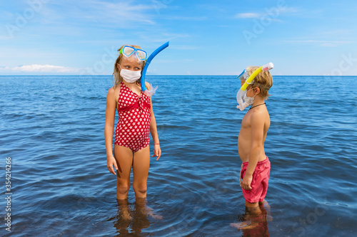 Fototapeta Kids in snorkeling mask wear surgical face mask on sea beach. Cancelled cruises, tours due coronavirus COVID 19 world epidemic. Travel ban for family vacation, tourism industry crisis at summer 2020 obraz