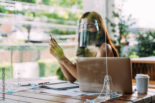 Young 20s Asian beautiful woman wearing a protective face shield and mask with partition in cafe restaurant Tableau sur Toile