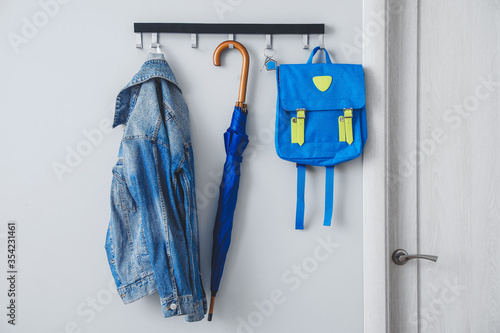 Obraz Umbrella with clothes and school backpack hanging on wall in hall - fototapety do salonu