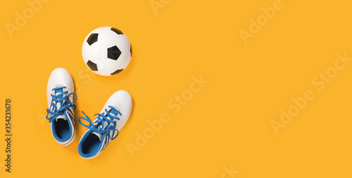 Canvastavla Soccer ball with white cleats against trendy yellow orange background, top view with copy space, football or sports class and tournament at school concept