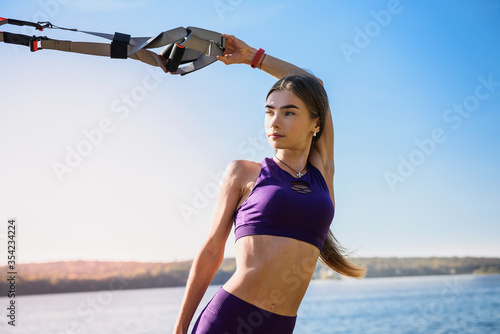 Fototapeta Young woman exercising with suspension trainer sling in park, near the lake