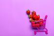 Leinwandbild Motiv Sweet ripe strawberry and shopping cart on color background