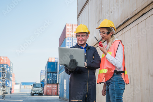 Two foreman man & woman worker working checking at Container cargo harbor holding laptop computer and using  to loading containers Wallpaper Mural