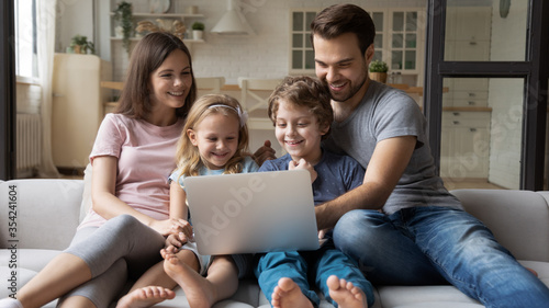 Foto Happy young caucasian family with small children relax on sofa in kitchen have f