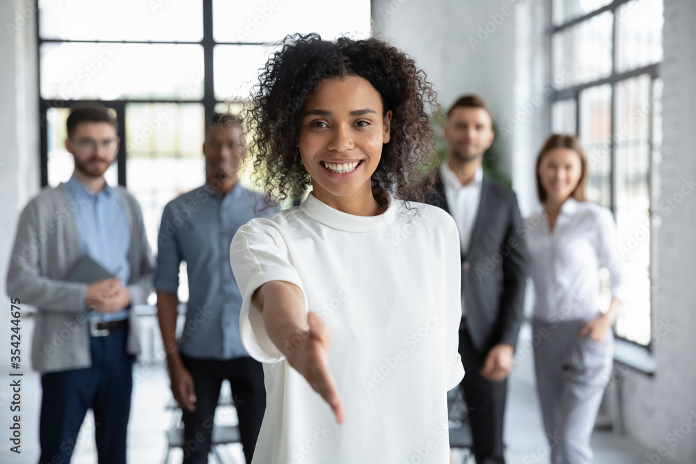 Fototapeta Head shot portrait smiling African American businesswoman offering handshake, standing with extended hand in modern office, friendly hr manager or team leader greeting or welcoming new worker