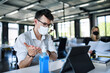 Leinwandbild Motiv Young people with face masks back at work in office after lockdown, disinfecting hands.