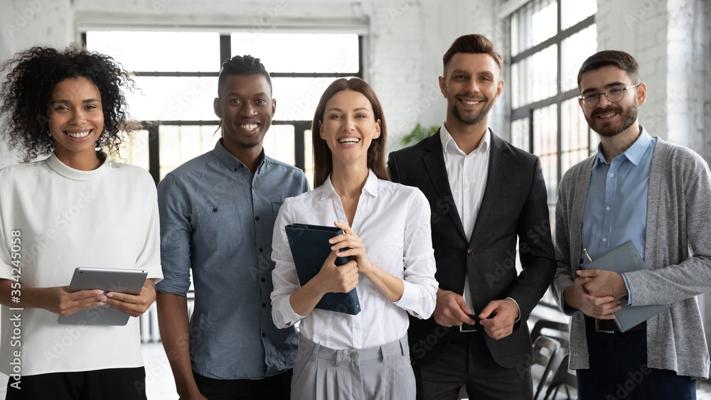 Fototapeta Corporate portrait successful smiling diverse employees team standing in office, posing for photo with confident businesswoman team leader executive, looking at camera, unity and cooperation