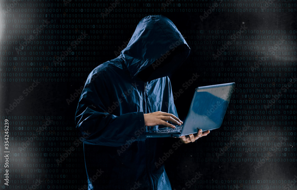 Fototapeta Internet crime concept,Hooded hacker using laptop in dark room