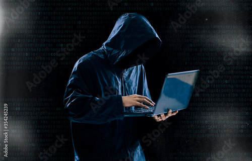 Internet crime concept,Hooded hacker using laptop in dark room Canvas