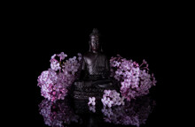 Black Buddha Framed By Pink Lilac Flowers On A Black Background With Reflection