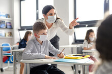Teacher And Children With Face Mask Back At School After Covid-19 Quarantine And Lockdown.