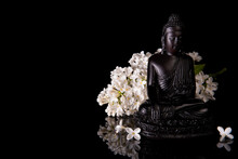 Black Buddha Framed By White Lilac Flowers On A Black Background With Reflection