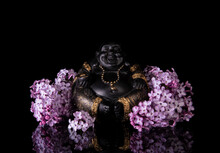 Chinese Laughing Buddha Hotei Or Budai Framed By Pink Lilac Flowers On A Black Background With Reflection