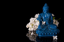 Blue Medicine Buddha Framed By White Lilac Flowers On A Black Background With Reflection