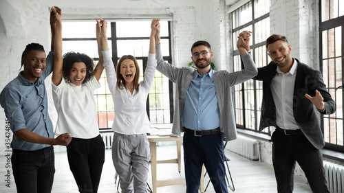 Obraz Excited diverse business people celebrating success, holding raised hands, looking at camera, smiling overjoyed employees team rejoicing achievement, laughing and screaming with joy in office room - fototapety do salonu