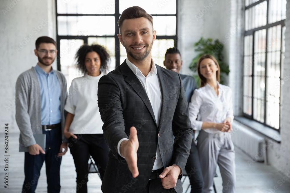 Fototapeta Head shot portrait confident smiling businessman offering hand for handshake, looking at camera, friendly hr manager team leader welcoming new worker, making agreement or great deal