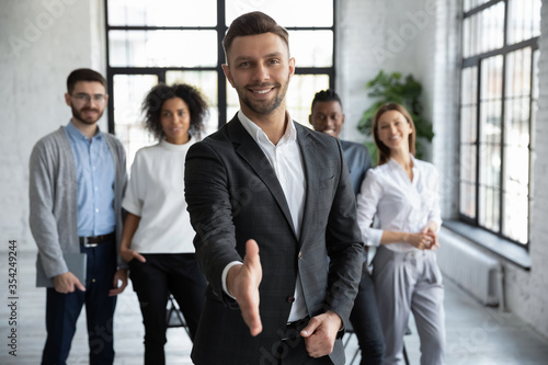 Head shot portrait confident smiling businessman offering hand for handshake, looking at camera, friendly hr manager team leader welcoming new worker, making agreement or great deal