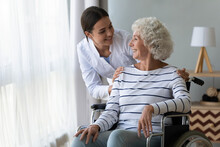 Smiling Disabled Elderly Woman Sitting In Wheelchair Talking With Caring Young Nurse In Living Room, Older Generation Receive Homecare Physical And Moral Support, Caregiving And Rehabilitation Concept