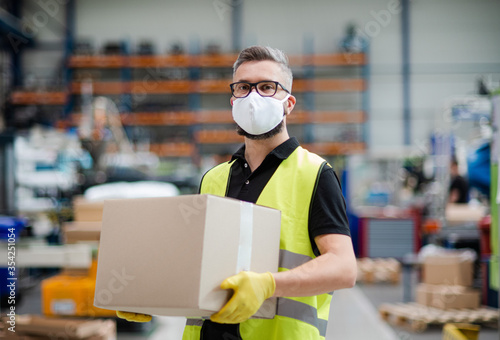 Leinwand Poster Man worker with protective mask working in industrial factory or warehouse