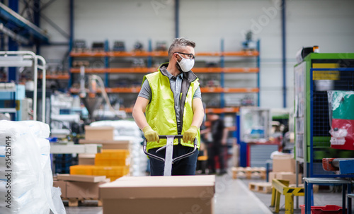 Cuadros en Lienzo Man worker with protective mask working in industrial factory or warehouse